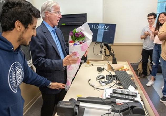 Sterling Professor of Economics William Nordhaus receives flowers from his intermediate macroeconomics class on Oct. 8, 2018 — the morning his Nobel Prize in Economic Sciences was announced. (Photo credit: Mara Lavitt)
